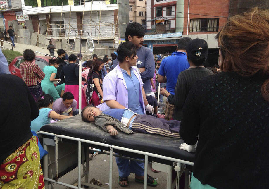 An injured child receives treatment outside Medicare Hospital in Kathmandu, Nepal, Saturday, April 25, 2015. A strong magnitude-7.9 earthquake shook Nepal's capital and the densely populated Kathmandu Valley before noon Saturday, causing extensive damage with toppled walls and collapsed buildings, officials said. (AP Photo/ Niranjan Shrestha)