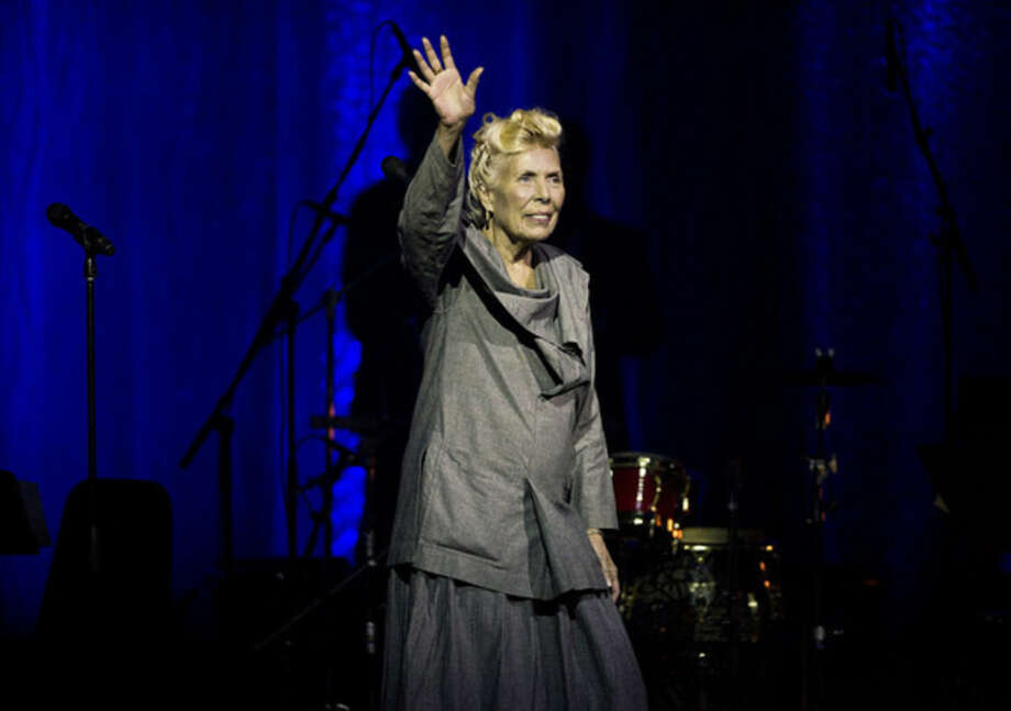 FILE - In this June 18, 2013 file photo, Joni Mitchell waves to the crowd during her 70th birthday tribute concert as part of the Luminato Festival at Massey Hall in Toronto. A woman identified as Mitchell's friend of more than 44 years, Leslie Morris, stated in a Tuesday, April 28, 2015, court filing in Los Angeles that the legendary folk singer is unconscious and unable to care for herself. A doctor's declaration accompanying Morris' petition to be named Mitchell's conservator states the singer-songwriter will not be able to attend any court hearings for at least four to six months, but offers no additional details on Mitchell's illness or prognosis. (Aaron Vincent Elkaim/The Canadian Press, File)
