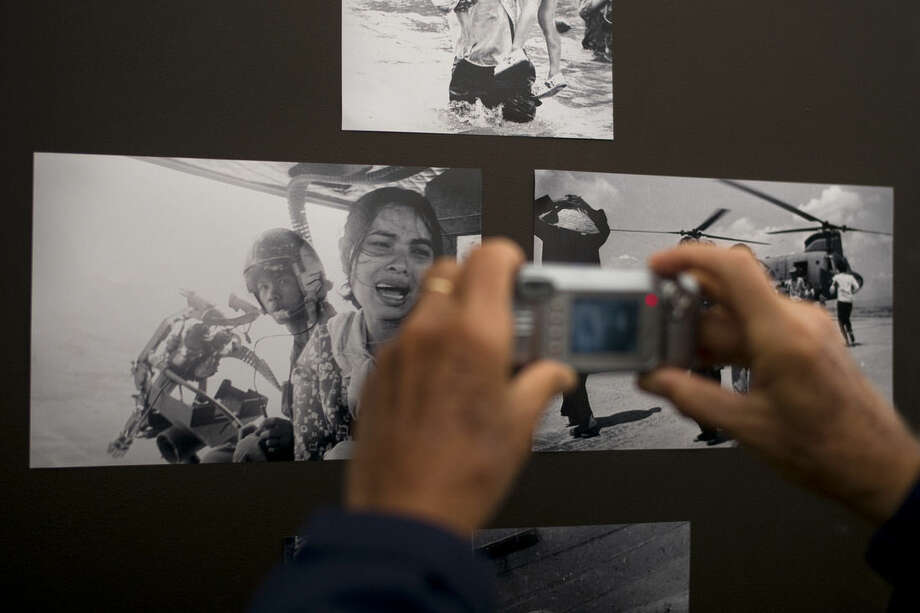 In this Saturday, April 25, 2015 photo, a Vietnamese man takes pictures of black and white photographs from the Vietnam War displayed at an event commemorating the 40th anniversary of the fall of Saigon held at Bolsa Grande High School in Garden Grove, Calif. Forty years since the fall of Saigon and the end of the Vietnam War, the thousands who fled their collapsing country still remember what they lost, but also take the moment to think about what they've gained as they rebuilt their lives in the U.S. (AP Photo/Jae C. Hong)