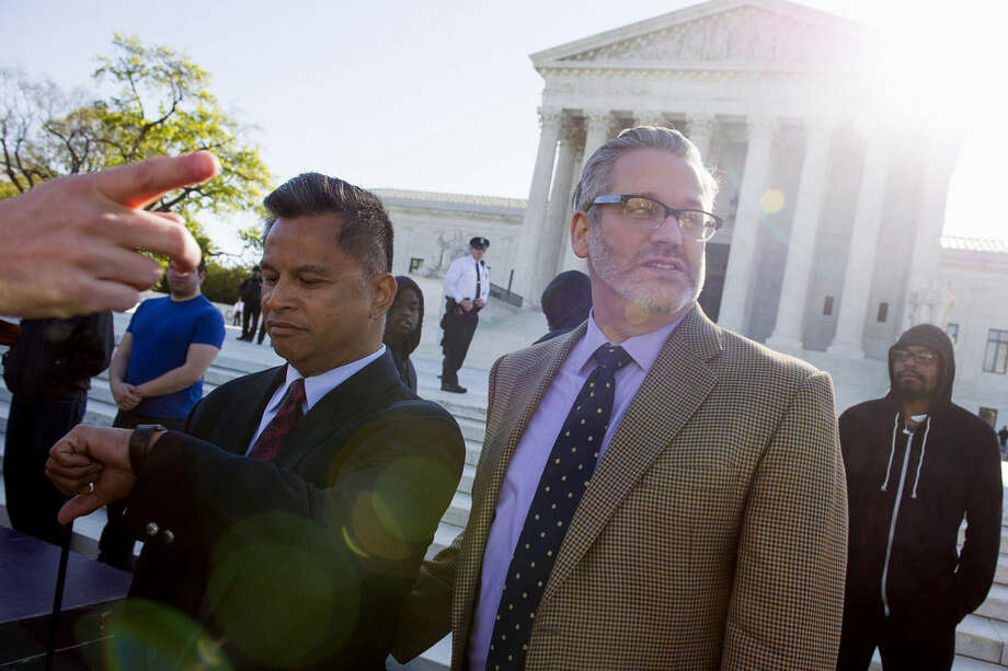 Plaintiffs John Espejo, left, and his husband Matthew Mansell, of Franklin, Tenn., prepare to enter the Supreme Court in Washington, Tuesday, April 28, 2015. The Supreme Court is set to hear historic arguments in cases that could make same-sex marriage the law of the land. The justices are meeting Tuesday to offer the first public indication of where they stand in the dispute over whether states can continue defining marriage as the union of a man and a woman, or whether the Constitution gives gay and lesbian couples the right to marry. (AP Photo/Cliff Owen)