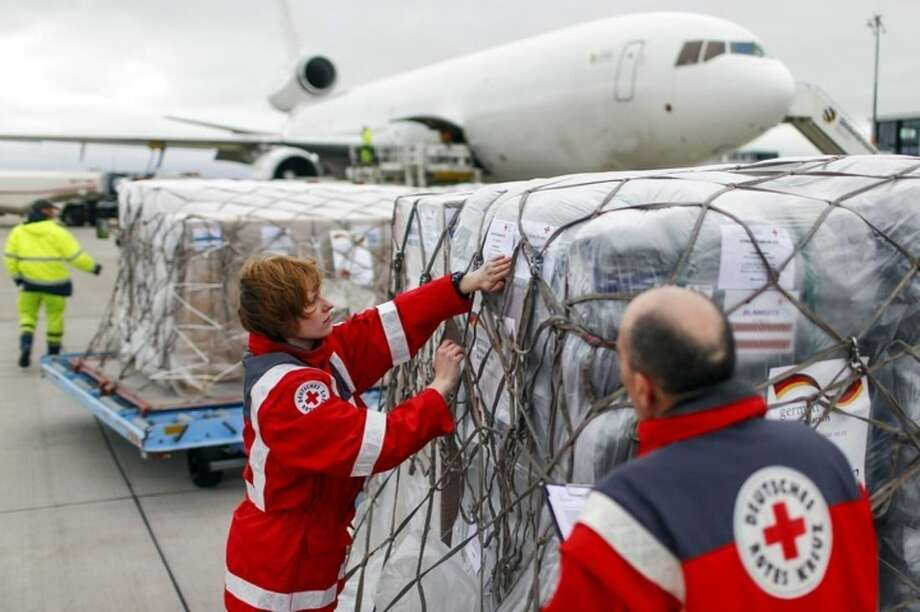 Workers of the German Red Cross (DRK) prepare a load of humanitarian aid for victims of the earthquake in Nepal, in front of an aircraft at Schoenefeld airport outside Berlin Monday, April 27, 2015. The flight will carry around 60 tonnes of supplies for the victims. (Hannibal Hanschke/Pool Photo via AP)