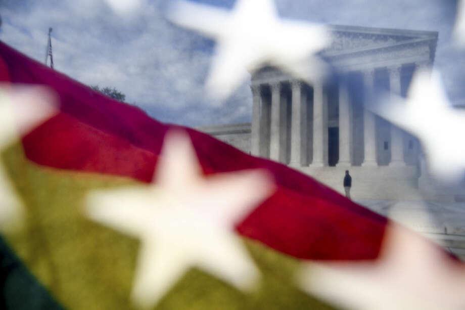 A rainbow colored flag, seen through an American flag, flies in front of the Supreme Court in Washington, Monday, April 27, 2015, as the Supreme Court is scheduled to hear arguments on the constitutionality of state bans on same-sex marriage on Tuesday. (AP Photo/Andrew Harnik)