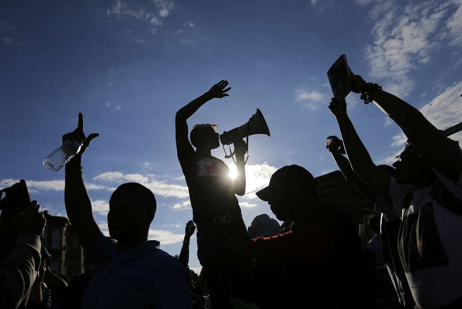 Demonstrators cheer in the intersection of West North and Pennsylvania Avenues in Baltimore on Saturday, May 2, 2015, one of the sites of Monday's rioting, as they march a day after charges were announced against the police officers involved in Freddie Gray's death. (AP Photo/David Goldman)