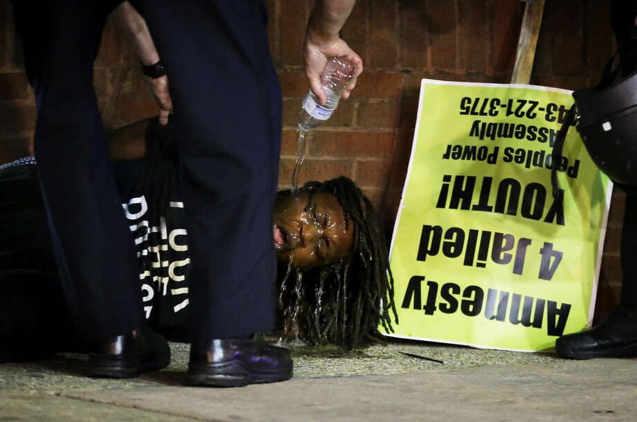 Police pour water over the face of a man after he was arrested and hit with pepper spray as police enforced a 10 p.m. curfew, Saturday, May 2, 2015, in Baltimore. (AP Photo/David Goldman)