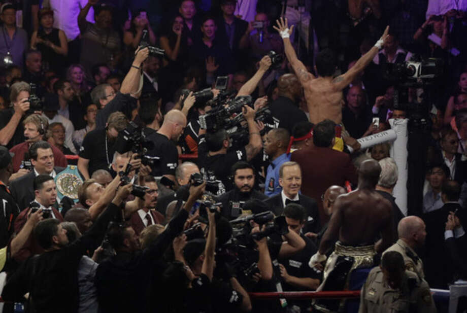 Floyd Mayweather Jr., bottom right, watches as Manny Pacquiao, from the Philippines, waves to the crowd at upper right after their welterweight title fight on Saturday, May 2, 2015 in Las Vegas. (AP Photo/Eric Jamison)