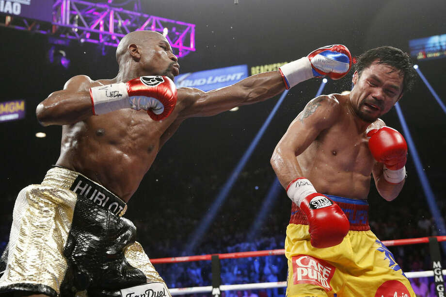 Floyd Mayweather Jr., left, hits Manny Pacquiao, from the Philippines, during their welterweight title fight on Saturday, May 2, 2015 in Las Vegas. (AP Photo/John Locher)