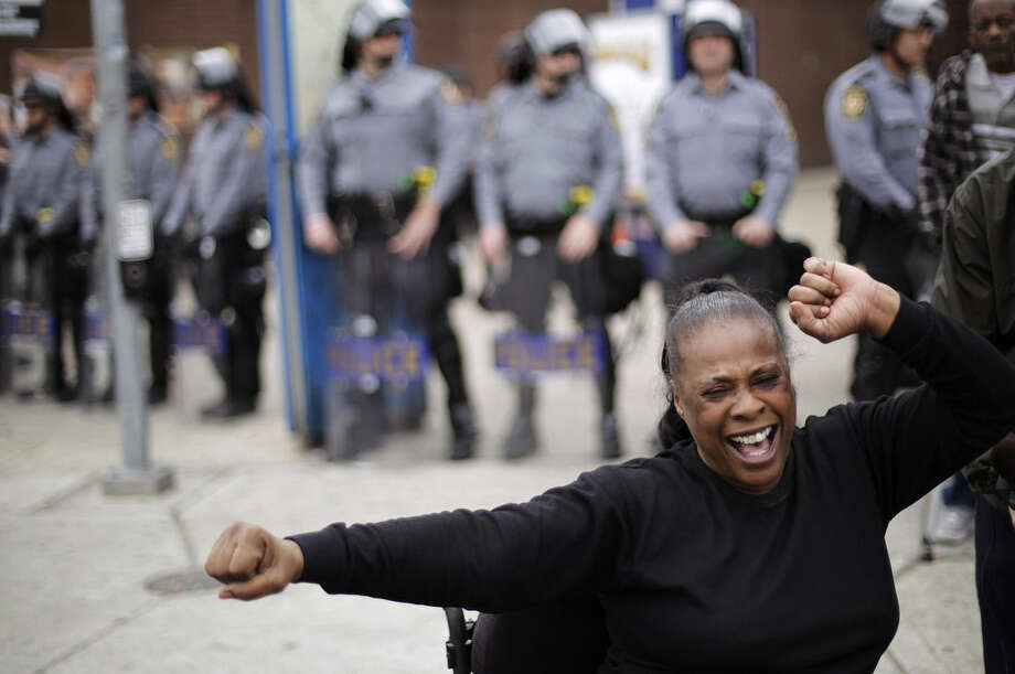 Lisa Mills celebrates in front of a line of police in riot gear on Friday, May 1, 2015, after State's Attorney Marilyn J. Mosby announced criminal charges against all six officers suspended after Freddie Gray suffered a fatal spinal injury while in police custody in Baltimore. Mosby announced the stiffest charge, second-degree depraved heart murder, against the driver of the police van. Other officers faced charges of involuntary manslaughter, assault and illegal arrest. (AP Photo/David Goldman)