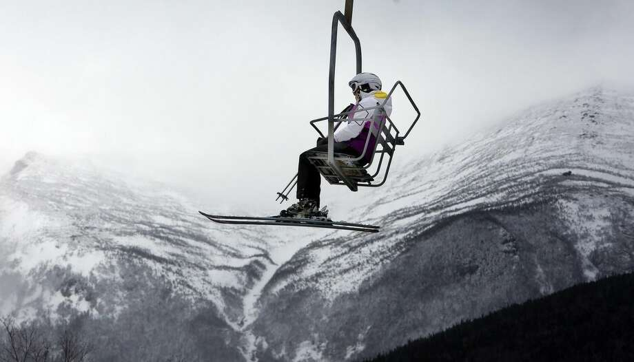 In this photo taken Saturday April 25, 2015 a skier rides the chairlift with part of Mount Washington seen in the background at Wildcat ski area in Gorham, N.H. Resorts in many northern New England ski areas are extending their season thanks to the abundance of snow. (AP Photo/Jim Cole)