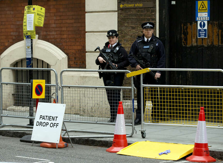 Armed police guard the front entrance of the Lindo Wing of St. Mary's Hospital, as Kate, Duchess of Cambridge has arrived to give birth to her second child in London, Saturday, May, 2, 2015. (AP Photo/Alastair Grant)