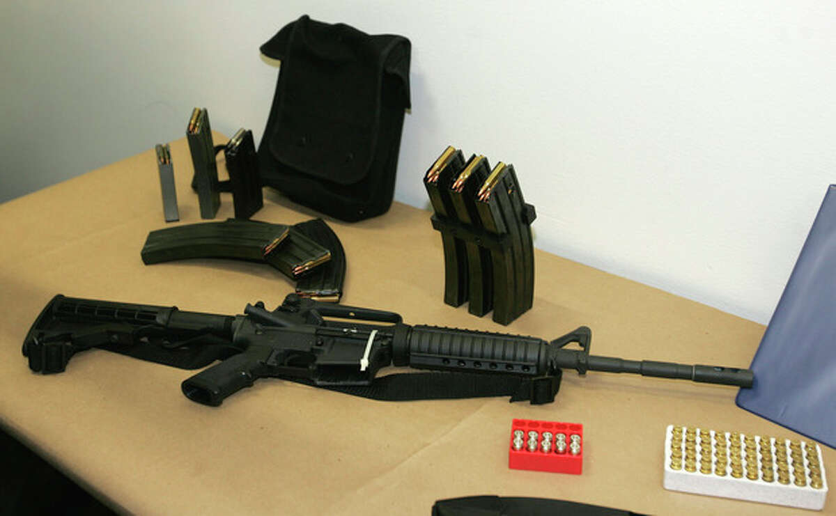 FILE - This March 27, 2006 file photo, shows a Bushmaster AR-15 semi-automatic rifle and ammunition on display at the Seattle Police headquarters in Seattle. (AP Photo/Ted S. Warren, File)
