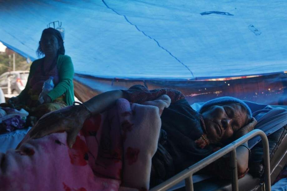 Nepalese patients stay inside a makeshift tent outside a hospital following Tuesday's earthquake in Kathmandu, Nepal, Wednesday, May 13, 2015. Thousands of fear-stricken people spent the night out in the open as a new earthquake killed dozens of people and spread more misery in Nepal, which is still struggling to recover from a devastating quake nearly three weeks ago. (AP Photo/Niranjan Shrestha)