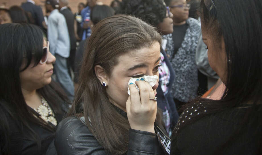 """Sarah Leighton wipe away tears during a memorial at Medgar Evers College to mourn the loss of Derrick E. Griffith, the college's dean of student affairs, Thursday, May 14, 2015. Griffith, 42, of Brooklyn, was among the victims in Amtrak's train derailment. Leighton, who knew Griffith while she worked as a volunteer in the student affairs office, said """"I didn't really have a father figure growing up, but he was that father figure for me."""" (AP Photo/Bebeto Matthews)"""
