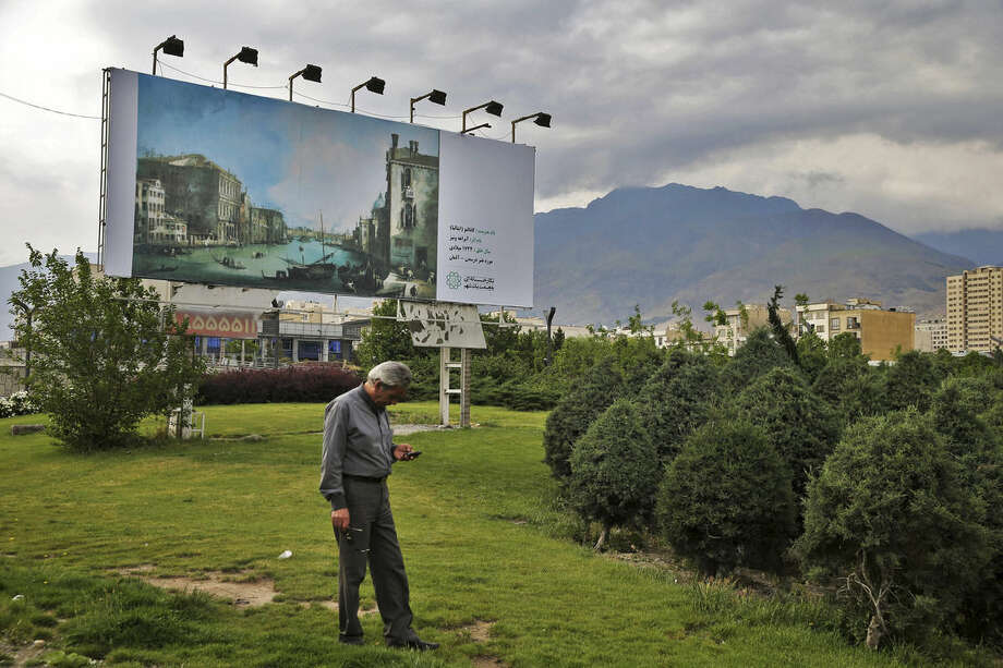 In this photo taken on Sunday, May 10, 2015, an Iranian man checks his mobile in front of a billboard showing a painting by Italian painter Canaletto, at the side of a highway in Tehran, Iran. In an unusual move by Tehran's mayor, hundreds of copies of famous artworks - both of world masters and Iranian artists - have been plastered on some 1,500 billboards across the city, transforming the Iranian capital into a gigantic, open-air exhibition. (AP Photo/Ebrahim Noroozi)