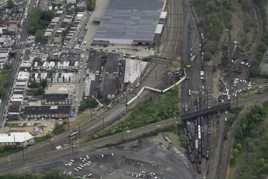 In this aerial photo, emergency personnel work at the scene of a deadly train wreck, Wednesday, May 13, 2015, in Philadelphia. Federal investigators arrived Wednesday to determine why an Amtrak train jumped the tracks in the wreck, Another body has been pulled from the wreckage of an Amtrak train derailment in Philadelphia, increasing the death toll to at least seven. (AP Photo/Patrick Semansky)