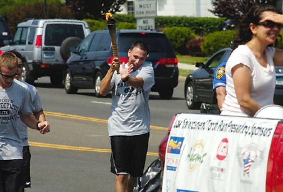 Norwalk police officer Phil Taborda carries the torch during the 2011 Law Enforcement Torch Run to benefit Special Olympics Friday morning. Hour photo / Erik Trautmann