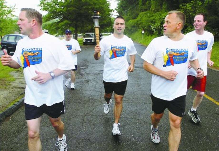 Wilton and state police runs with the Special Olympics torch as part of the torches journey through the area to mark the begining of the games this month. Hour photo / Erik Trautmann