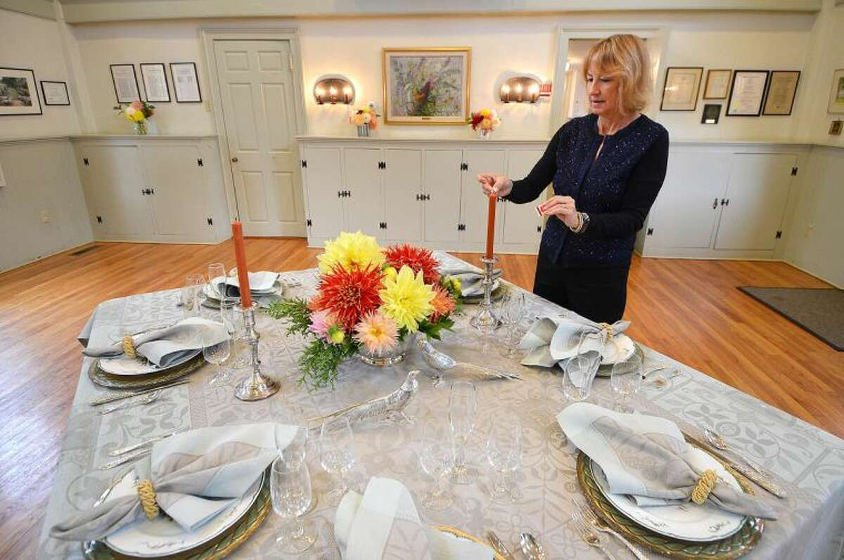 Hour Photo/Alex von Kleydorff Wilton Garden Club President Nan Merolla lights some candles to set the scene inside the Old Town Hall which is available for event rentals