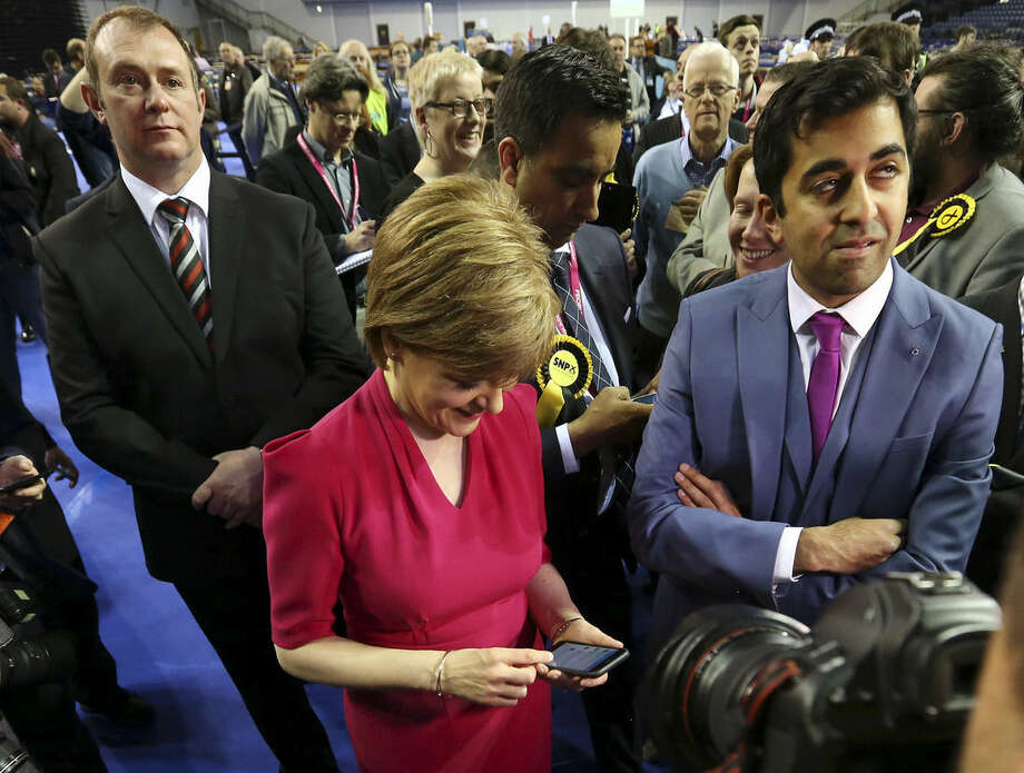 First Minister of Scotland and Scottish National Party leader Nicola Sturgeon, front left, checks her mobile phone for results of her party at the count of Glasgow constituencies for the general election in Glasgow, Scotland, Friday, May 8, 2015. The Conservative Party fared much better than expected in Britain's parliamentary election, with an exit poll and early returns suggesting that Prime Minister David Cameron would remain in his office at 10 Downing Street. The opposition Labour Party led by Ed Miliband took a beating, according to the exit poll, much of it due to the rise of the separatist Scottish National Party. (AP Photo/Scott Heppell)