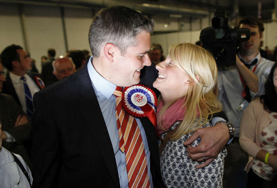 Democratic Unionist Party (DUP) candidate for East Belfast Gavin Robinson celebrates with his wife Lyndsay after being elected MP for East Belfast at the Kings Hall count centre, in Belfast, Northern Ireland, Friday, May 8, 2015. The DUP could prove to be an important link as Britain's most unpredictable general election in decades with polls showing the two biggest parties running in a virtual dead heat. (AP Photo/Peter Morrison)