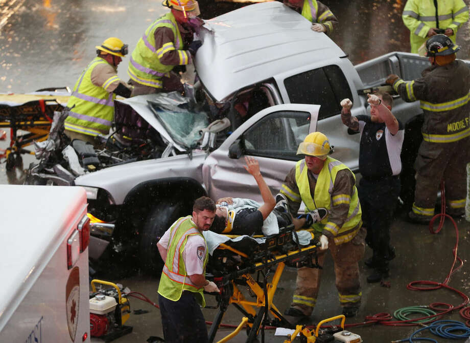 The driver of a pickup truck which crashed in severe weather on Interstate 35 gestures to his rescuers after being cut from the truck in Moore, Okla., Wednesday, May 6, 2015. Forecasters declared a tornado emergency for Moore. (AP Photo/Sue Ogrocki)