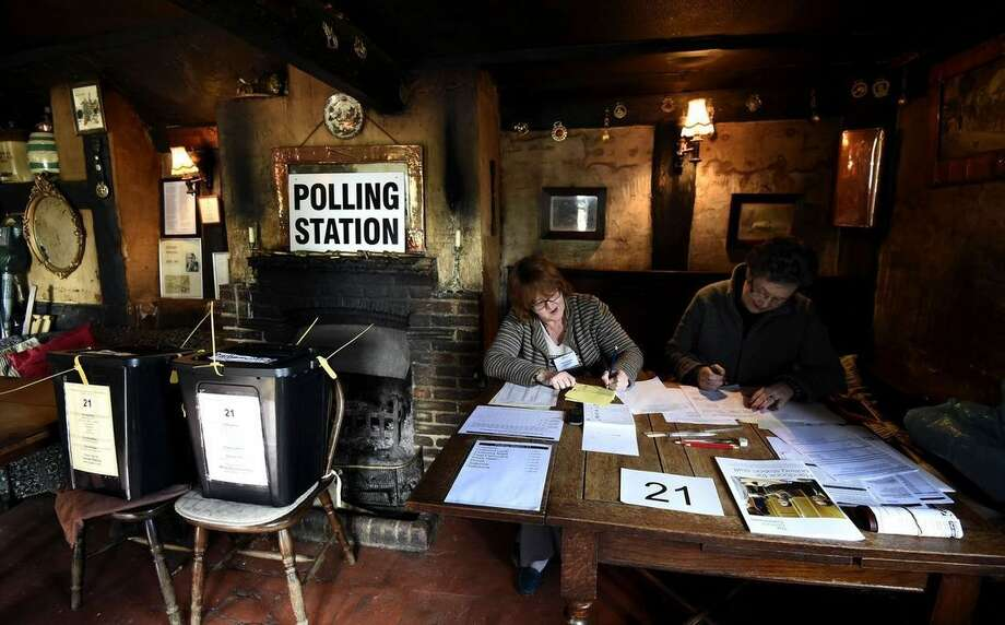 Election officials work at a table inside the White Horse Inn, which is being used as a polling station in Priors Dean, southern England Thursday May 7, 2015. Polls have opened in Britain's national election, a contest that is expected to produce an ambiguous result, a period of frantic political horse-trading and a bout of national soul-searching. (Andrew Matthews/PA via AP) UNITED KINGDOM OUT NO SALES NO ARCHIVE