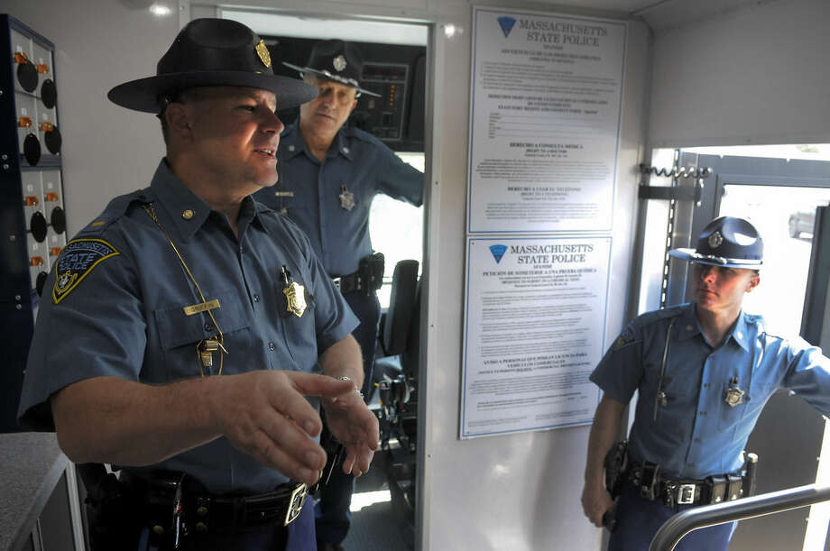 Lt. Daniel Griffin, left, of the Massachusetts State Police, explains the process of their DUI Mobile Command Center during a news conference in Windsor, Conn., Monday, May 4, 2015. State police across New England launched the region's first coordinated crackdown on speeding and failing to wear seat belts. (John Woike/Hartford Courant via AP)