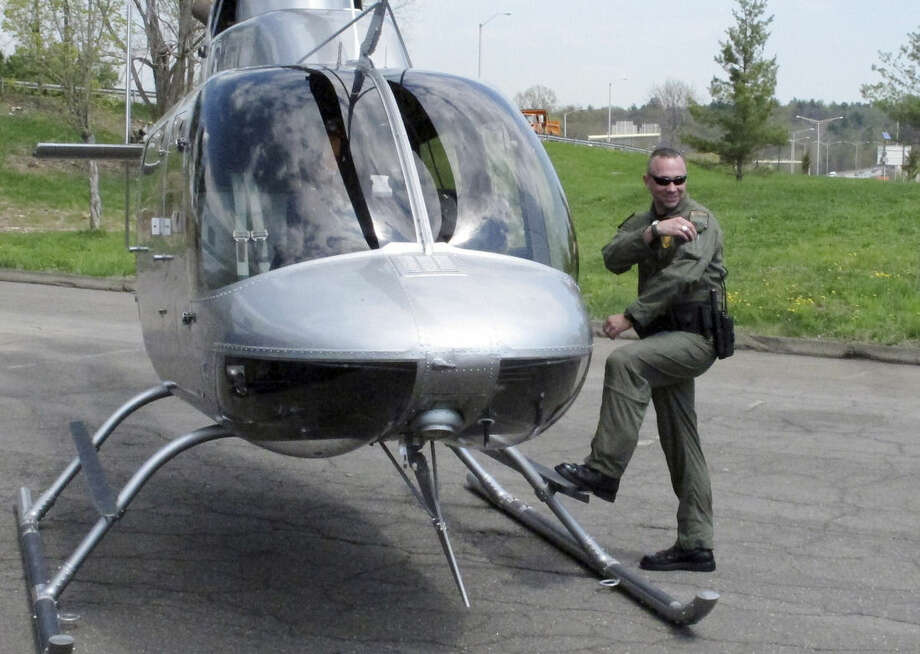 Connecticut State Police trooper Adam McOmber stands next to a police helicopter during a news conference in Windsor, Conn., Monday, May 4, 2015. Officials announced a New England-wide crackdown on speeding and failing to wear seat belts. Troopers in all six states will be beefing up enforcement on interstates 91 and 95 this week. (AP Photo/Dave Collins)