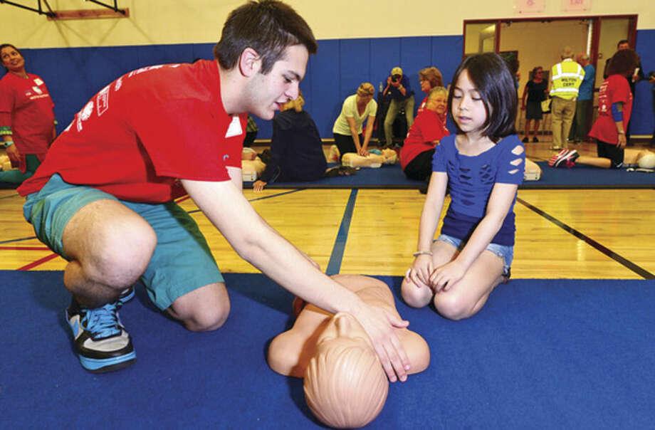 Westport EMT and Hands for Life volunteer Ben Muller teaches Aimee Millman proper CPR technique at the Westport Weston YMCA Sunday.