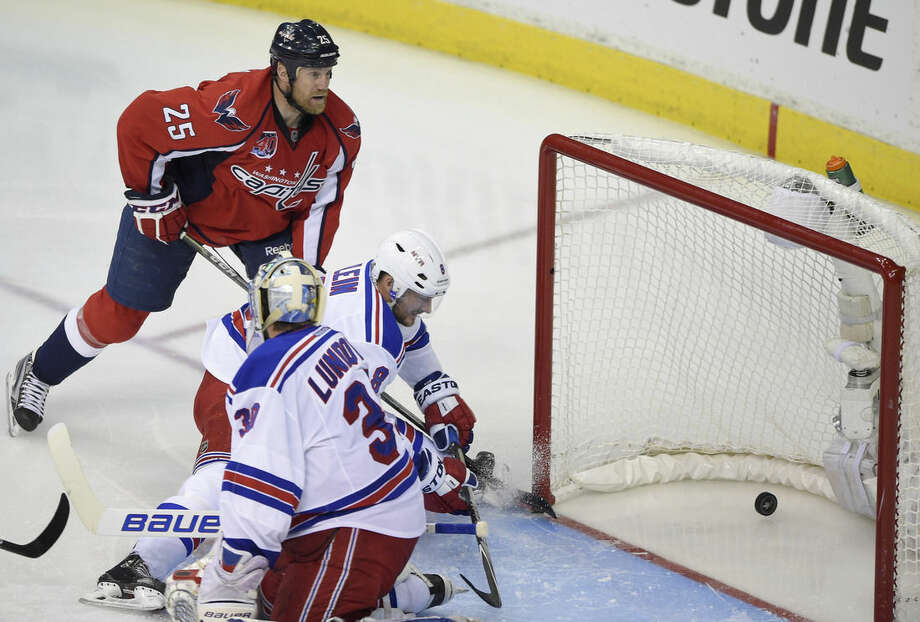 Washington Capitals left wing Jason Chimera (25) scores a goal against New York Rangers goalie Henrik Lundqvist (30), from Sweden, and Kevin Klein (8) during the second period of Game 6 in the second round of the NHL Stanley Cup hockey playoffs, Sunday, May 10, 2015, in Washington. (AP Photo/Nick Wass)