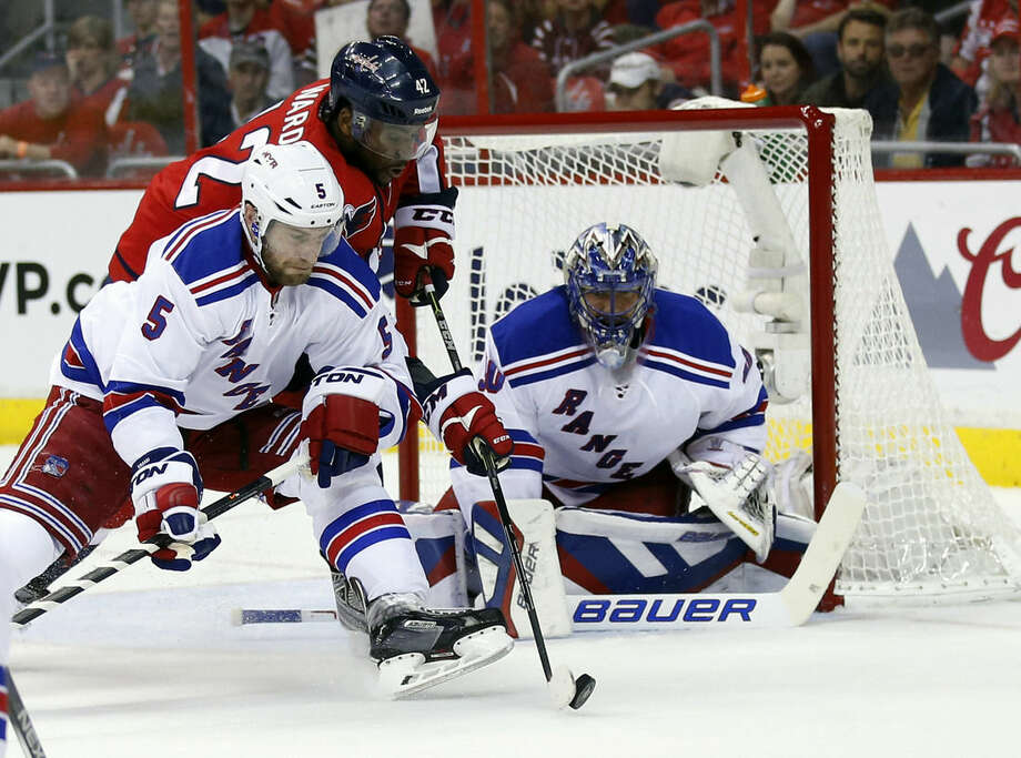 New York Rangers defenseman Dan Girardi (5) goes for the puck against Washington Capitals right wing Joel Ward (42) with goalie Henrik Lundqvist (30), from Sweden, during the first period of Game 6 in the second round of the NHL Stanley Cup hockey playoffs, Sunday, May 10, 2015, in Washington. (AP Photo/Alex Brandon)