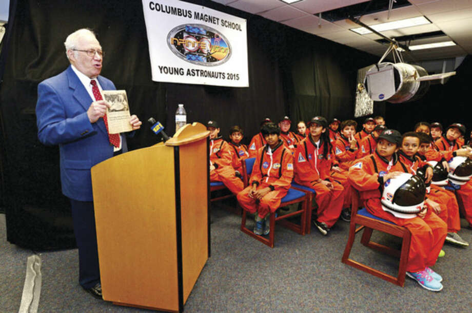 Hour photo / Erik Trautmann Program founder Art Perchino holds up a newspaper clipping of the first mission as the Young Astronauts program at Columbus Magnet School celebrates the landing of their latest mission, Infinite Vision, and the programs 20th anniversay Friday morning at the school.