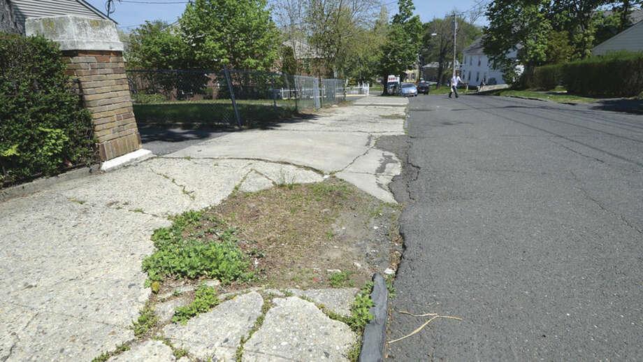 Hour Photo/Alex von Kleydorff Weeds grow along a section of sidewalk on Golden Hill St.