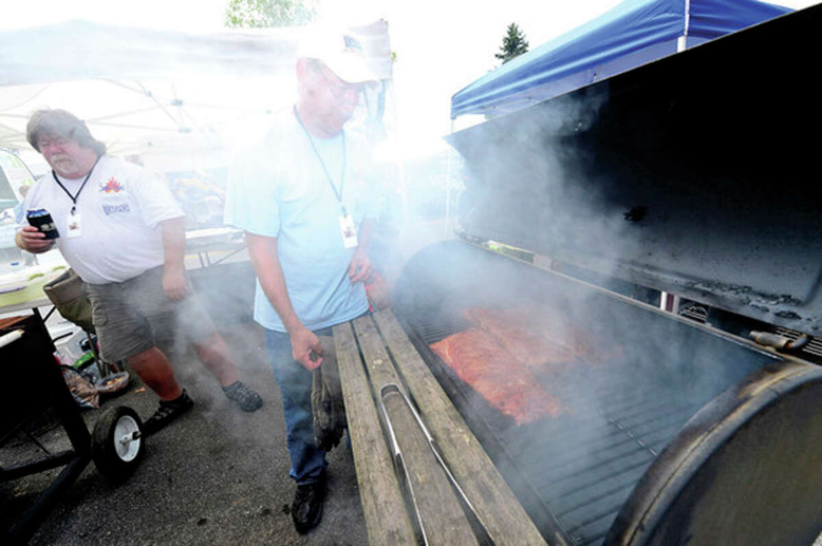 Joe Huzina and Keth Swanson with the Smokin Spice team get their ribs ready for competition during Westport's 5th annual Blues Views and BBQ at Jesup Green Saturday. Hour photo / Erik Trautmann