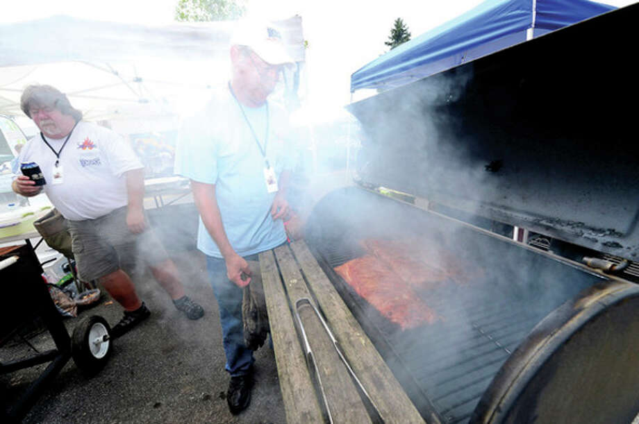 Joe Huzina and Keth Swanson with the Smokin Spice team get their ribs ready for competition during Westport's 5th annual Blues Views and BBQ at Jesup Green Saturday.Hour photo / Erik Trautmann / (C)2013, The Hour Newspapers, all rights reserved