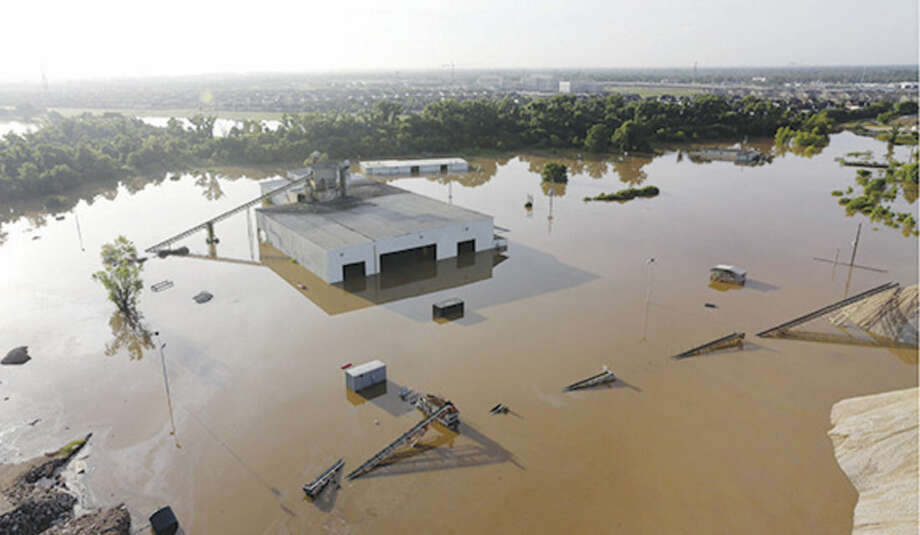 AP photo/David J. PhillipA business is surrounded by floodwaters near the Brazos River Saturday in Sugar Land, Texas. The Colorado River in Wharton and the Brazos and San Jacinto rivers near Houston are the main focus of concern as floodwaters moved from North and Central Texas downstream toward the Gulf of Mexico.