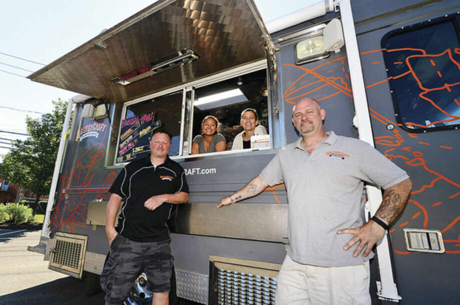 Hour photo / Erik Trautmann Michael Haren, owner of Lobstercraft, and his partner Trond Fletcher and their staff, Laura Cuseo and Liz Machette with one of their food trucks.