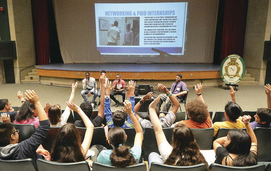 Hour Photo/Alex von Kleydorff Norwalk High School students raise their hands in answer to a question from the PTECH students during a forum at the high school Thursday
