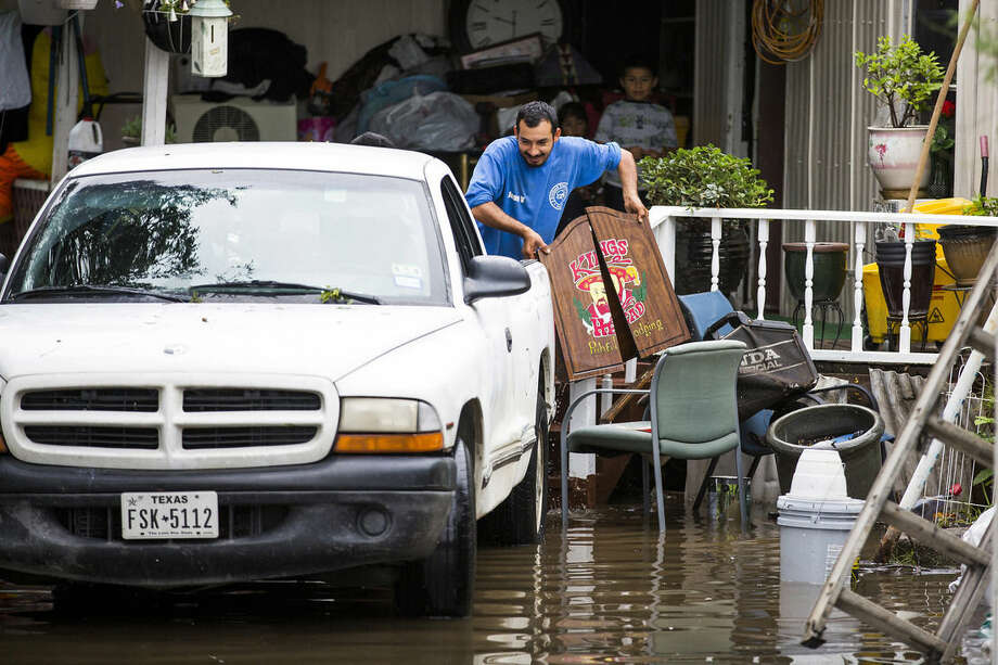 Residents load their belongings into a truck as the rising waters from Mountain Creek surround their home in the Willow Bend mobile home park on Sunday, May 24, 2015, in Grand Prairie, Texas. The Dallas/Forth Worth received more than three inches of rain since midnight, with more reportedly on the way. (Smiley N. Pool/The Dallas Morning News via AP)