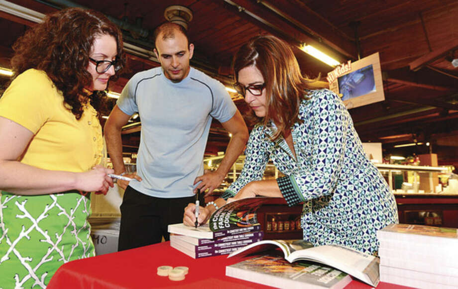 Hour photo / Erik Trautmann Local authors Tracey Medeiros and Christy Colasurdo sign copies of their new cookbook, The Connecticut Farm Table Cookbook, for Jon Cafasso at Stew Leonard's Norwalk store Saturday.