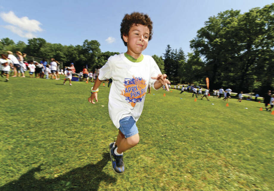 Hour photo / Erik Trautmann Fox Run Elementary School students including kindergartner Javier Valle participate in their first ever Apex Fun Run benefit Wednesday in lieu of their annual walk-a-thon. The fundraiser will benefit the renovations of the school library.