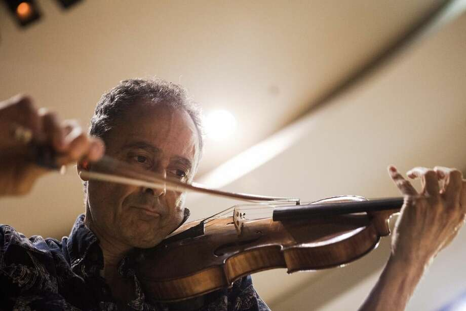 In this photo taken Wednesday, May 27, 2015, Grammy Award-winning American violinist Eugene Drucker, plays his violin during a rehearsal concert at the Music Hall in Raanana, central Israel. In 1933, the violinist Ernest Drucker left the stage midway through a Brahms concerto in Cologne at the behest of Nazi officials, in one of the first anti-Semitic acts of the new regime. Now, more than 80 years later, his son, Eugene, has completed his father's interrupted work. With tears in his eyes, Drucker performed an emotional rendition of the Brahms Violin Concerto in D Major, Op. 77, over the weekend with the Raanana Symphonette Orchestra. (AP Photo/Dan Balilty)