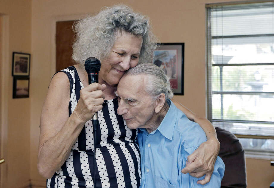 In this May 11, 2015 photo, Saundra Karp hugs her husband, Al, after a rehearsal at their home in North Miami Beach, Fla. The Karps, along with their son, Larry, perform old standards locally as the Karp Family band to ease stress and help raise money to save their home from foreclosure. (AP Photo/Alan Diaz)