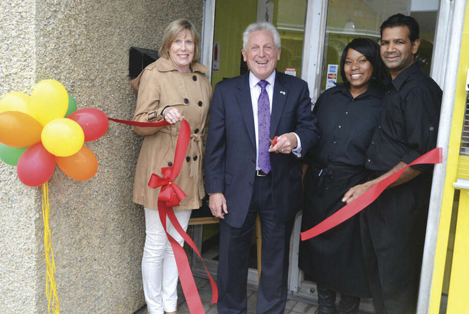 Hour Photo/Alex von Kleydorff Norwalk Mayor Harry Rilling and Director of Economic Development Liz Stocker cut the ribbon with owners Tanisha and Sean Willaims at their new Fragrant Basil Juice Cafe