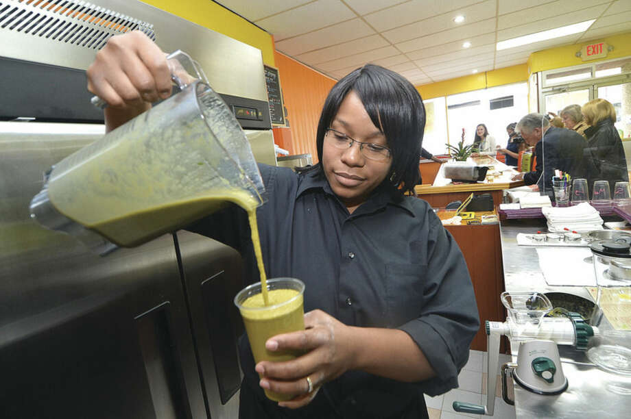 Hour Photo/Alex von Kleydorff Owner Tanisha Williams pours a fresh made smoothie, 'Adrenaline Rush' at the new Fragrant Basil Juice Cafe
