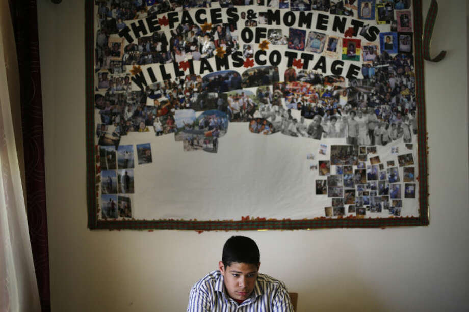 "In this Thursday, April 24, 2014 photo, Angel B., 15, sits under a board displaying past and present residents of Williams Cottage at the Children's Village campus in Dobbs Ferry, N.Y. A shift of mission by the facility, which was founded in 1851, reflects a growing consensus within the child-welfare field that institutional settings for foster children - while sometimes necessary - should be used sparingly. CEO Jeremy Kohomban says, ""We need to use the residential system as a short-term emergency room, then get kids back to the community."" (AP Photo/Seth Wenig)"