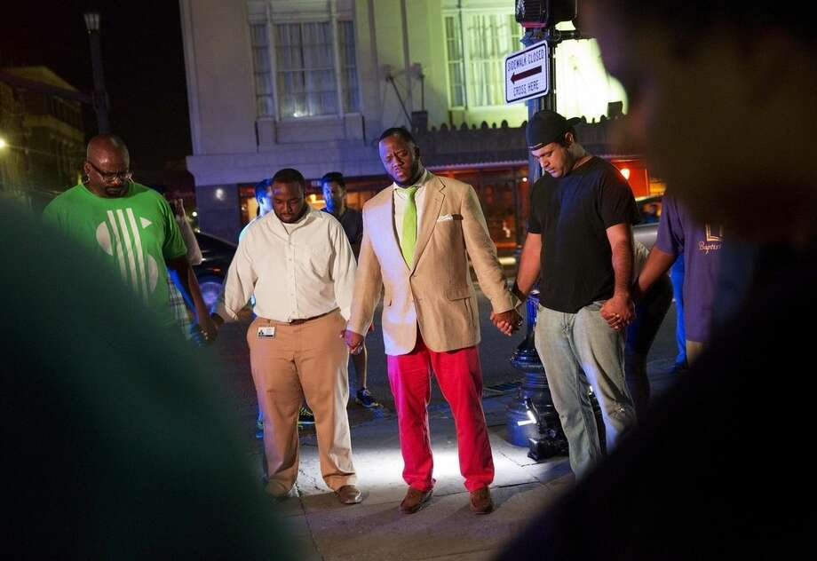 Worshippers gather to pray down the street from the Emanuel AME Church following a shooting Wednesday, June 17, 2015, in Charleston, S.C. The current brick Gothic revival edifice, completed in 1891 to replace an earlier building heavily damaged in an earthquake, was a mandatory stop for the likes of Booker T. Washington and the Rev. Martin Luther King Jr. Still, Emanuel was not just a church for the black community.(AP Photo/David Goldman)