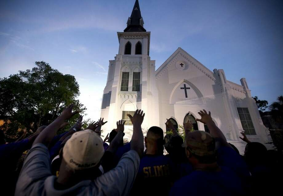 The men of Omega Psi Phi Fraternity Inc. lead a crowd of people in prayer outside the Emanuel AME Church, Friday, June 19, 2015, after a memorial in Charleston, S.C. Thousands gathered at the College of Charleston TD Arena to bring the community together after nine people where shot to death at the church on Wednesday. The current brick Gothic revival edifice, completed in 1891 to replace an earlier building heavily damaged in an earthquake, was a mandatory stop for the likes of Booker T. Washington and the Rev. Martin Luther King Jr. Still, Emanuel was not just a church for the black community. (AP Photo/Stephen B. Morton)