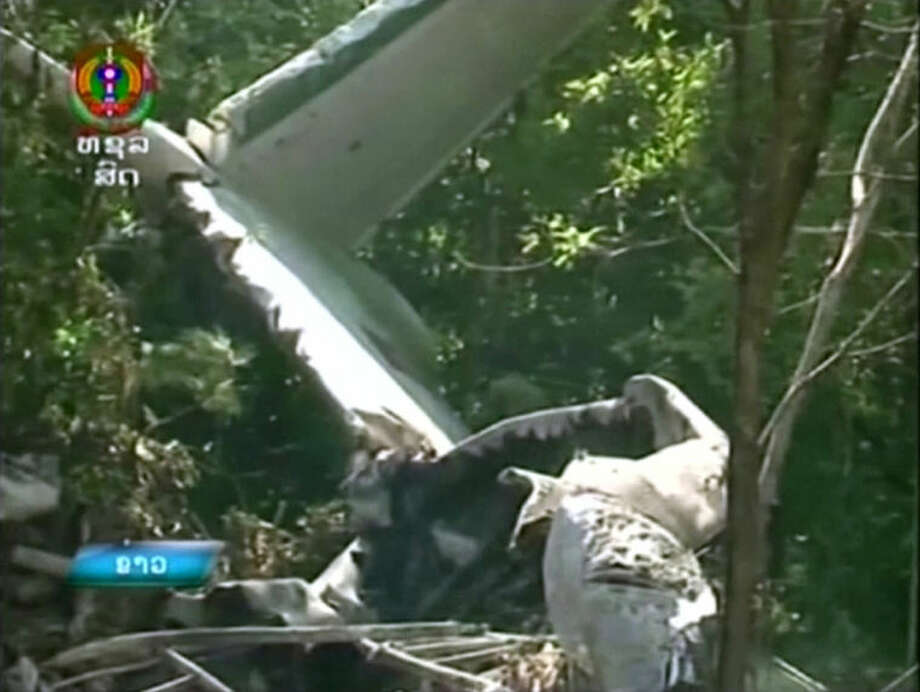 This image taken from video provided by Lao National TV, shows the wreckage of a Lao air force plane which crashed in a forested area of Xiangkhoung province, Laos Saturday, May 17, 2014. The Lao air force plane carrying senior government officials crashed Saturday, killing at least five people on board, including the country's Defense Minister Douangchay Phichit, Thai officials said. (AP Photo/Lao National TV via AP Video) LAOS OUT, TV OUT
