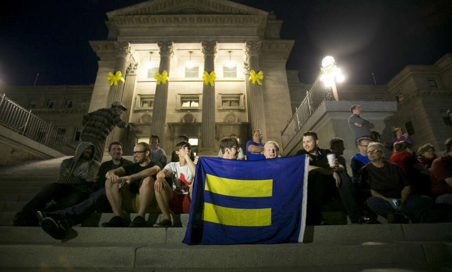 Same-sex marriage supporters gather on the steps of the Idaho Statehouse in Boise on Tuesday night May 13, 2014 after U.S. Magistrate Judge Candy Dale ruled earlier in the day that Idaho's ban on gay marriage is unconstitutional. (AP Photo/The Idaho Statesman, Kyle Green)