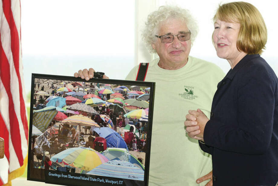Hour photo / Erik Trautmann Renown Westport photographer Larry Silver presidents a limited edtion photograph to CT DEEP Deputy Commsioner Susan Whalen during a ceremony for the newly renovated Sherwood Island State Park Pavillion Tuesday afternoon.